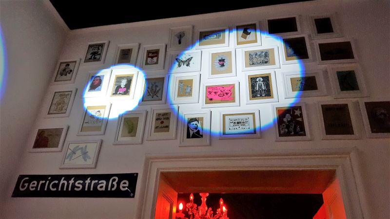 Art & Pizza Gallerie. Wand gefüllt mit Kunstdrucken früherer Veranstaltungen.