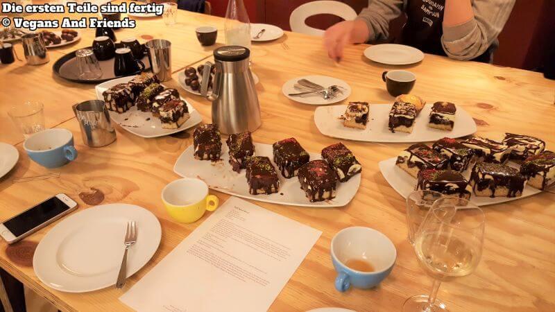 Vegan Baking Basics - Der Tisch wird gedeckt. Die Donauwellen sind fertig, auch die Nuss-Schoko-Kugeln. Kaffee und Tee stehen bereit und auch ein Gläschen Cremant. Ein Blatt mit Rezepten liegt am Tisch.