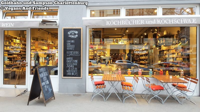 Goldhahn und Sampson Charlottenburg. Aussenansicht. Schaufenster, Markisen, davor zwei Tische und Stühle.