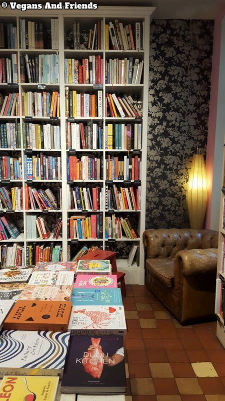 Goldhahn und Sampson Kochbücher. Riesen Auswahl. Regale mit Büchern, in der Ecke ein bequemer Ledersessel, in der Mitte des Raums ein großer Tische voll mit Büchern.