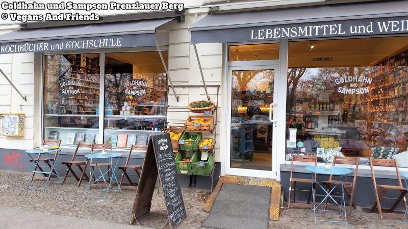 Goldhahn und Sampson Prenzlauer Berg. Aussenaufnahme. Schaufenster, Markisen, kleine runde Tische und Stühle davor. Neben dem Eingang ein Regal mit Obstkisten.