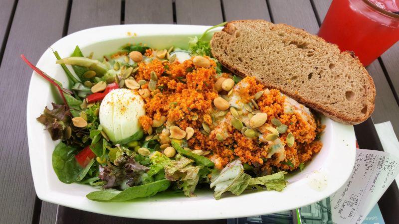 Little Green Rabbit Couscous Salat. In einer Schale mit verschiedenen Blattsalaten, Erdnüssen, Ei und Dressing serviert. Am Rand der Schale liegt eine Scheibe Brot.