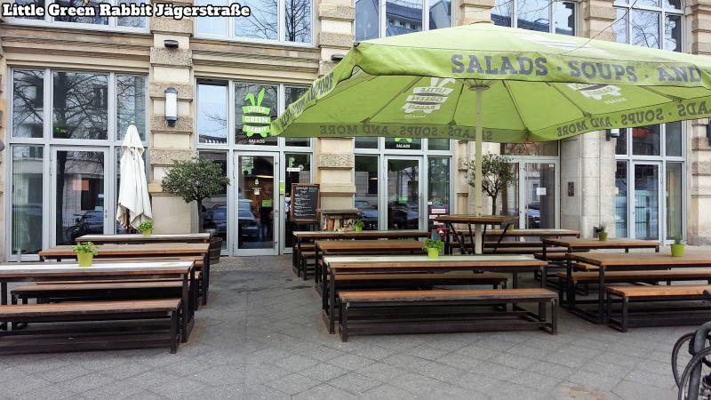 Little Green Rabbit Jägerstraße. Außenansicht. Auf dem Vorplatz lange Holztische und Bänke. Ein großer, grüner Sonnenschirm.
