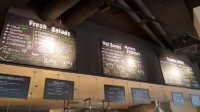 Little Green Rabbit Menütafeln. Über dem langen Tresen hängen zahlreiche Schilder mit dem Speiseangebot. Die Überschriften sind auf Englisch, die Speisen auf Deutsch, mit Vermerk ob vegan, mit Huhn oder Rind.