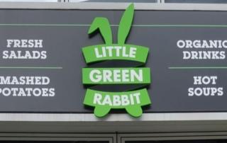"""Little Green Rabbit Schild über dem Eingang der Filiale am Checkpoint Charlie. Links steht: Fresh Salads und darunter mashed potatoes, in der Mitte auf einem grünen, stilisierten Hasen mit zwei langen Ohren """"Little Green Rabbit"""" und rechts organic drinks und darunter hot soups."""