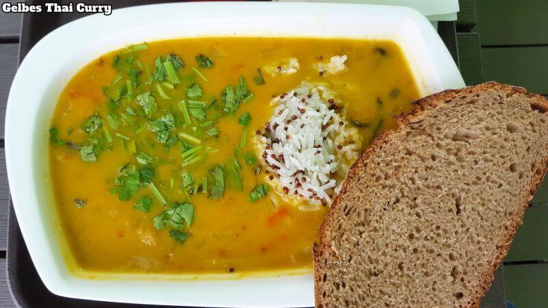 Little Green Rabbit Thai Curry. Teller aus Helicopterperspektive mit gelbe Curry mit frische Petersilie bestreut, rechts ragt ein Haufen Reis heraus und am rechten Tellerrand daneben liegt eine Scheibe Brot.