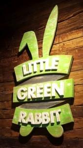 Little Green Rabbit Wandschild. Logo aus Holz grün mit weißen Buchstaben.