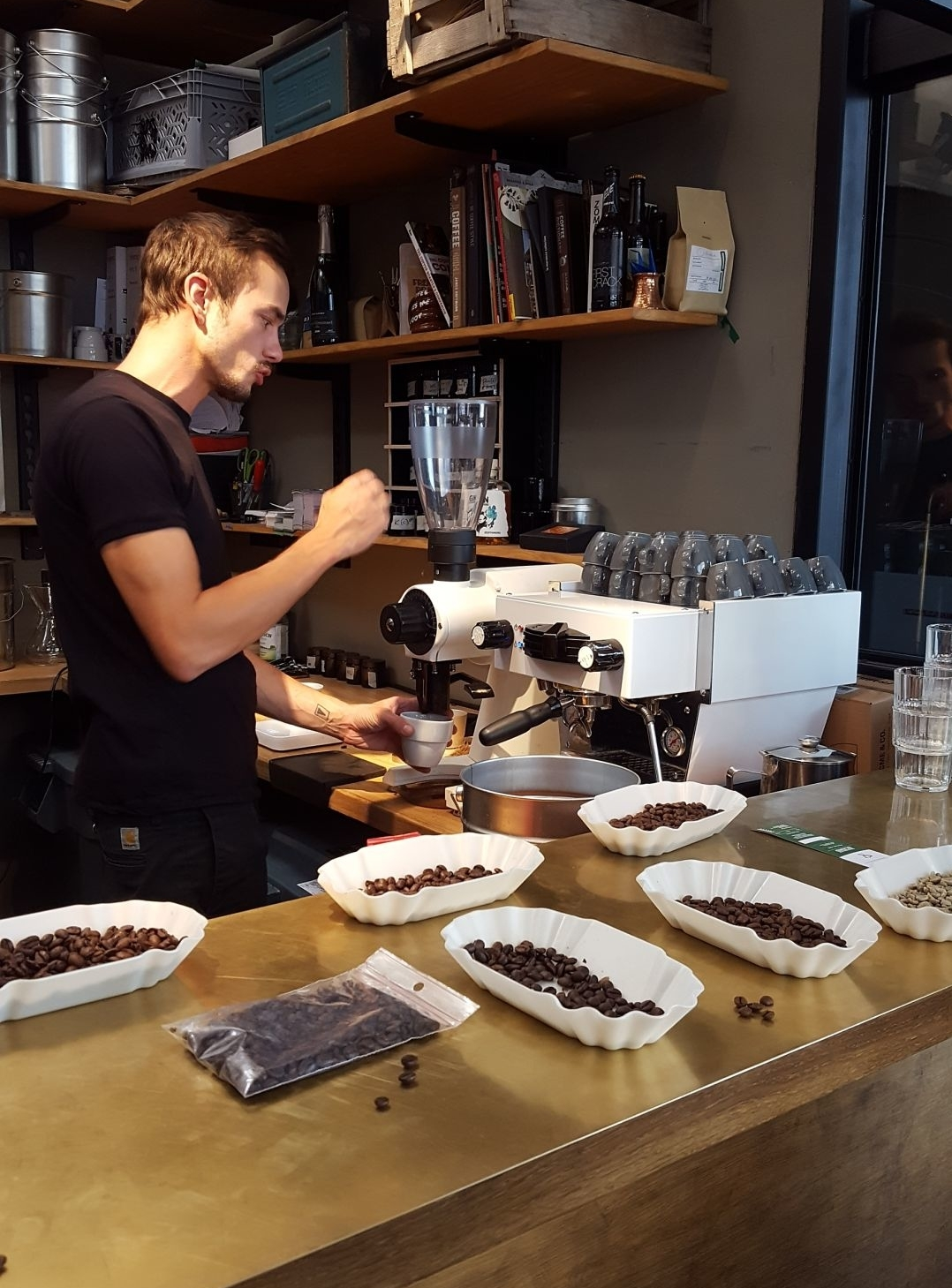 Philipp Reichel preparing coffee. At the coffee mill, weighing in the exact amount of coffee pouder.