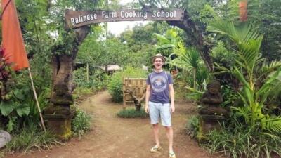 Pemula Bali Farm Cooking School. Ich stehe am Eingangstor. Auf dem Balken darüber steht: Balinese Farm Cooking School