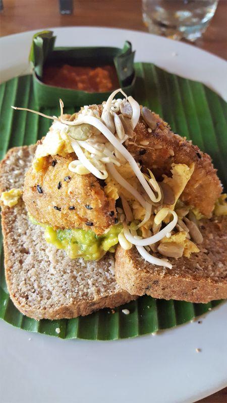 Bali Buda. Frühstück. Avocado Smash vegane Version mit knusprigem Tofu. Toast halbiert, geschichtet auf einem Bananenblatt belegt mit Avocado, Sprossen und gebratenem Tofu.