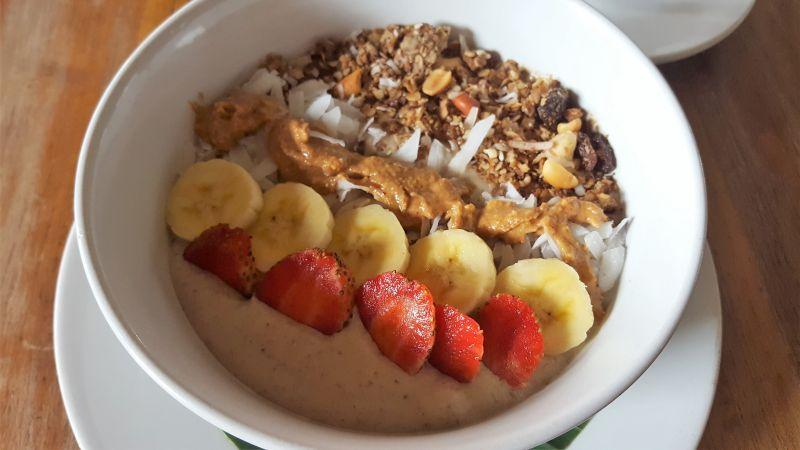 Bali Buda. Frühstück. Supercharger Smoothie Bowl mit Banane, bio Erdnussbutter, Haferflocken, Datteln und Kokosnuss dekoriert mit Erdbeeren, Bananascheiben, Kokosnuss und Granola.