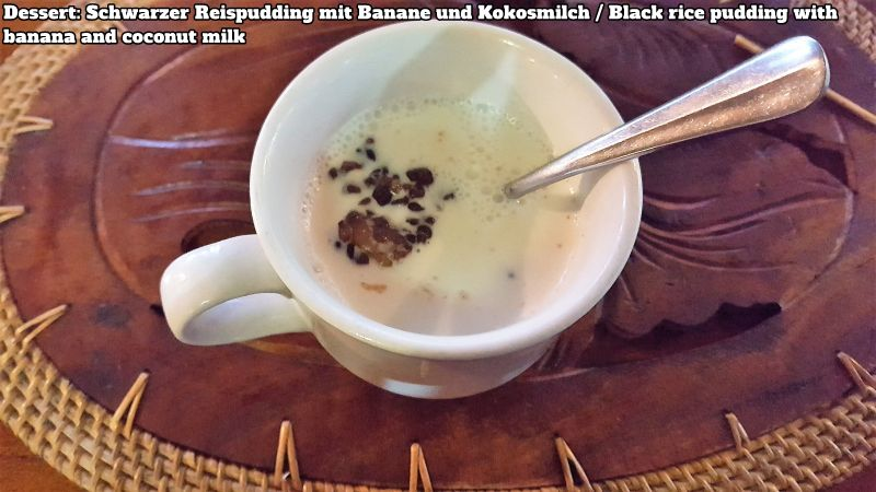 Bali Farm Cooking School. Black rice pudding with banana and coconut milk served in a cup with a spoon sticking in the pudding.