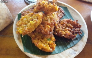 Bali Farm Cooking. Corn fritters served on a banana leaf on a wooden board.
