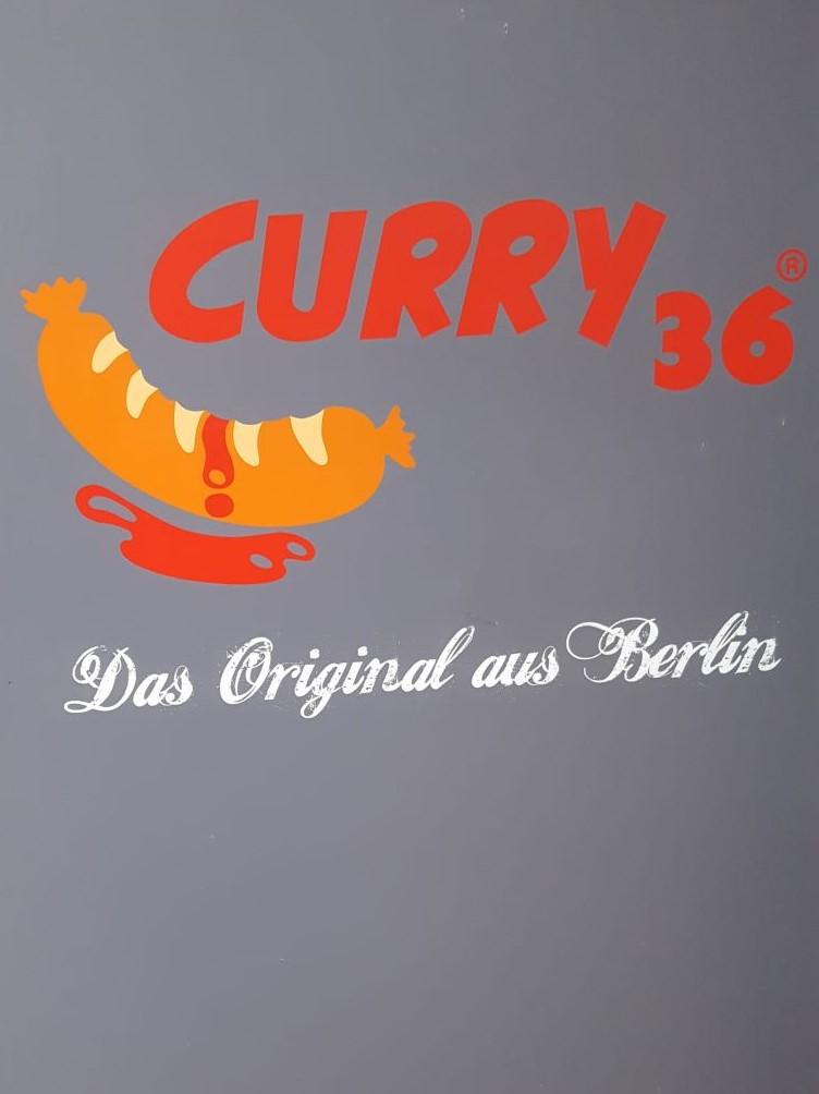 Curry 36. Das Original aus Berlin. Über der Aufschrift eine gemalte Currywurst mit heruntertropfender Soße.