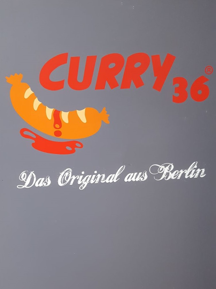 Curry 36. The original from Berlin. Above the line a painting of a currywurst with some sauce dripping down.
