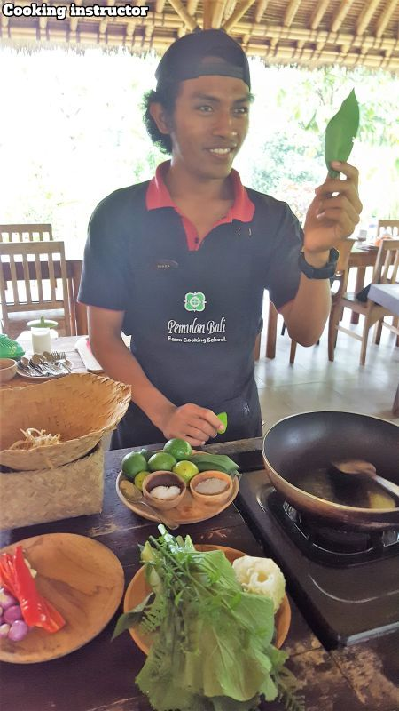 Bali Farm Cooking School. Deren our instructor with balinese bay in his hand.