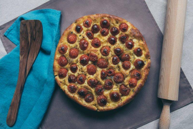 Foccacia & Panzerotti. Geschirrtuch, Holzlöffel, eine fertig gebackenes Foccacia gespickt mit Kirschtomaten und ein Nudelholz.