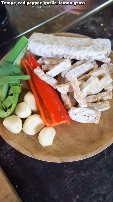 Bali Farm Cooking School. Tempe, garlic, red pepper, lemon grass on a wooden plate.