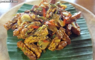 Bali Farm Cooking. Sweet and sour tempe. Fride tempe with vegetables served on a banana leaf on a wooden plate.