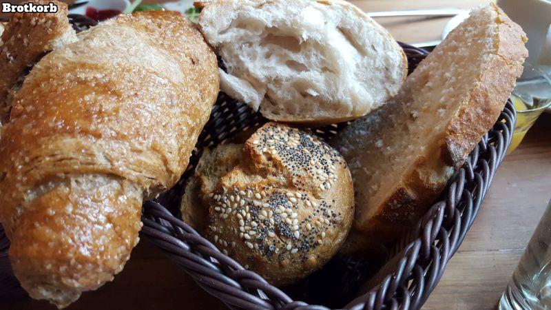 Zimt & Zucker Brotkorb. Himbeer-Hollunder Croissant, Weizensauerteigbrot, Brötchen und Brotscheibe.