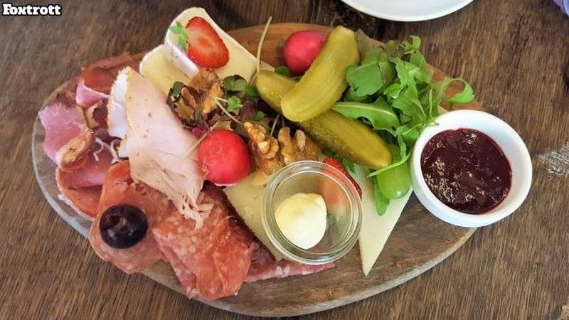 Zimt & Zucker Foxtrot breakfast. Oval wooden board with salami, turkey ham, raw ham, various cheeses, Spreewald gherkin, radishes, walnuts, strawberry, butter and jam in a little bowl.
