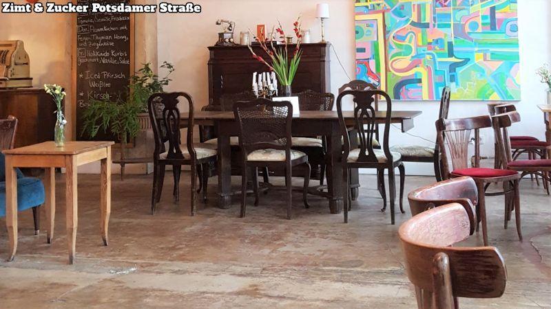 Zimt & Zucker Potsdamer Strasse. Roher Fußboden, rechts klassische Kaffeehausstühle mit rotem Samtsitzpolster, in der Mitte eine Esszimmergruppe, dahinter ein Piano an der Wand, rechts daneben ein buntes Gemälde.
