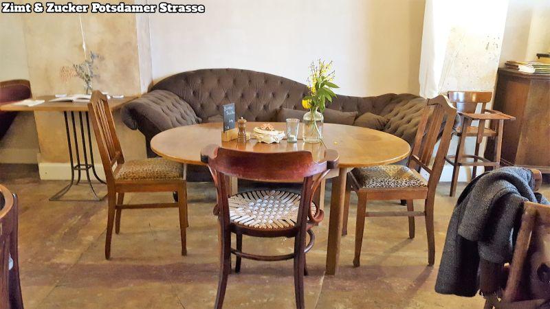 Zimt & Zucker Potsdamer Strasse Sitzgruppe. Ovaler Tisch mit Blumenvase, Pfeffermühle, Teelicht, rundherum 3 Stühle, an der Wand ein ausladendes Sofa.