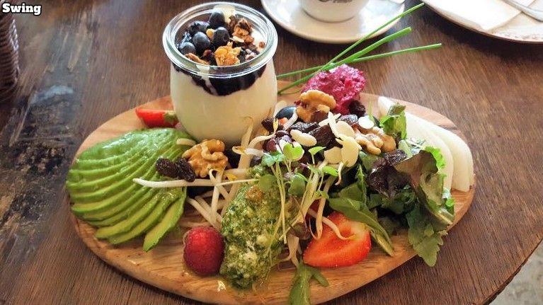 Zimt & Zucker Swing breakfast. Oval wooden board with vegan spreads, avocado and pear cut like a fan, jar of soy yoghurt, blueberries and granola, nuts, berries, sprouts, salad.