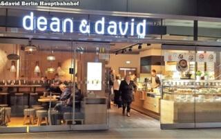 dean&david berlin hauptbahnhof. Blick von außen durch die Glasscheiben. Rechts zu sehen, die Theke mit den Sandwiches, Wraps etc. im Anschluss nach hinten der Tresen. Links sieht man verschiedene Sitzgelegenheiten und unterschiedliche Hängeleuchten.