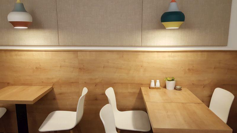 dean&david Inneneinrichtung. Zwei bunte Lampen die einen Lichtkegel nach unten auf die Tische werfen. Weiße Stühle, Tische und die halbhohe Wandvertäfelung in hellem Holz.