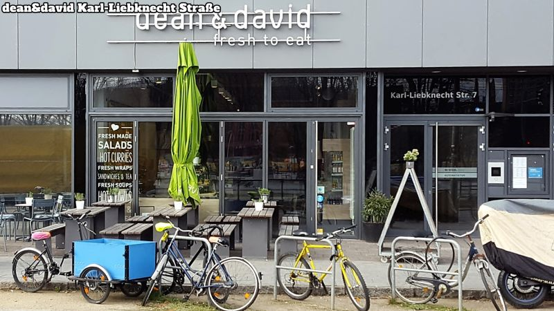 dean&david Karl-Liebknecht Straße Berlin. Am Straßenrand Fahrräder. Am Gehsteig vor dem Restaurant Tische und Bänke. Dazwischen ein grüner, abgespannter Sonnenschirm.