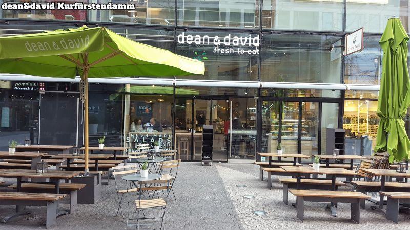 dean&david Kurfürstendamm. Viele Tische und Bänke, auch ein paar kleine, runde Tische mit Stühlen. 2 grüne Sonnenschirme, einer aufgespannt, der andere nicht.