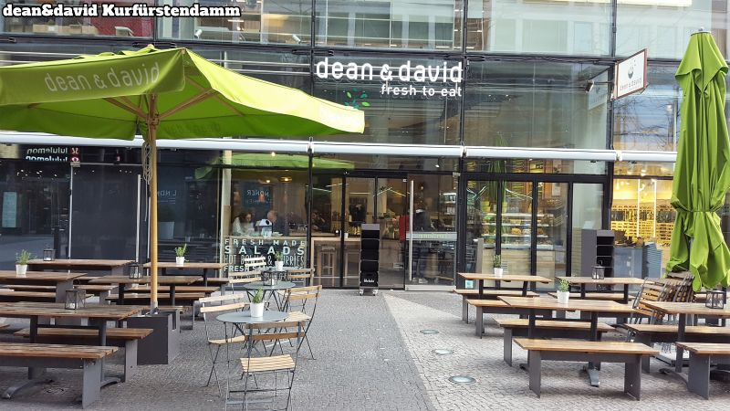 dean&david Kurfürstendamm. Lots of tables and benches, also a few small round tables with chairs. 2 green parasols, one unfolded the other one folded up.