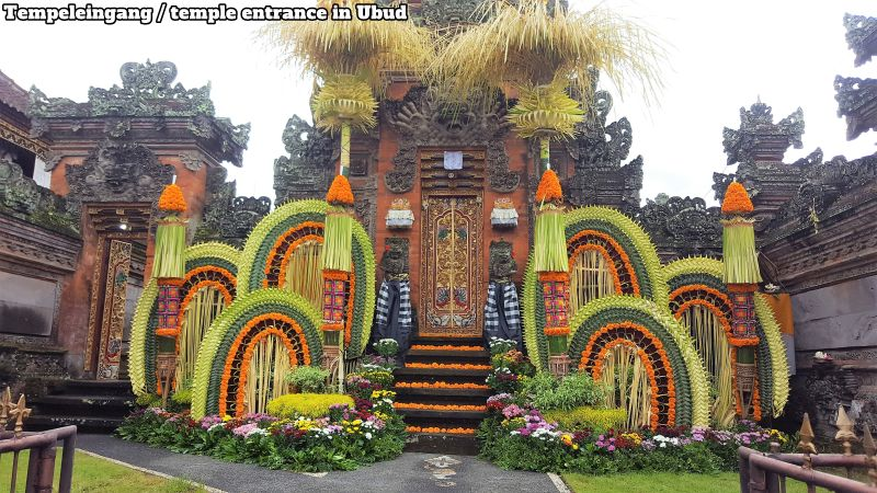 Tempel/temple in Ubud. Neben dem Markt. Next to the market. Mit Blumen und Geflecht geschmücktes Eingangstor. Entrance gate decorated with flowers and wickerwork.