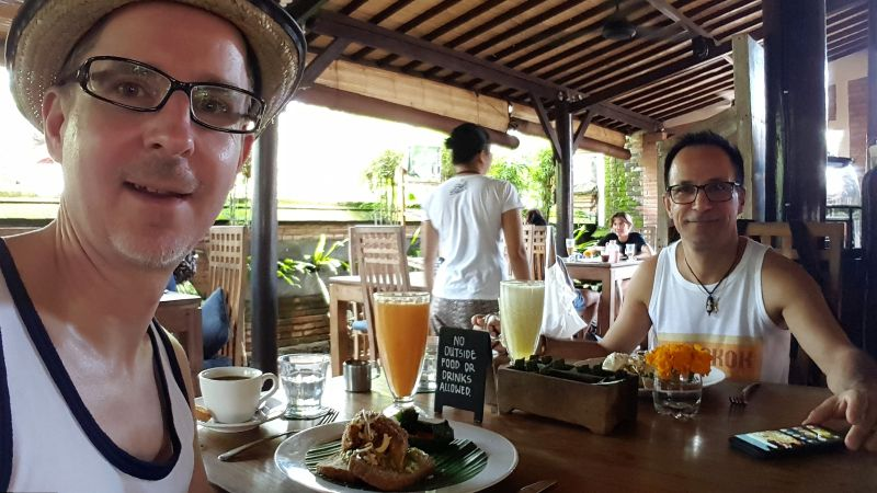 Bali Buda. Frühstück. José und ich beim Frühstücken. Gedeckter Tisch mit Smashed Avocado, frischen Säften (Papaya und Ananas), Kaffee und Wasser.