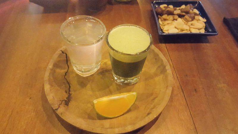 Cafe Vida Canggu. Wheatgrass shot with a piece of lemon and a glass of coconut water for rinsing.