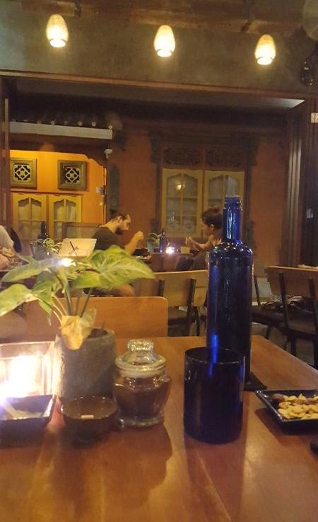 Cafe Vida. Das Interieur ist hauptsächlich aus dunklem Holz. Man bekommt automatisch ein Flasche Wasser auf den Tisch gestellt.