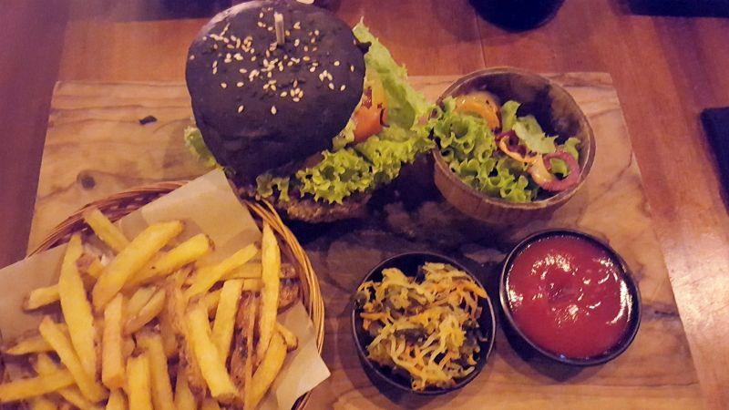 Cafe Vida Canggu. Veggie Burger mit gegrilltem, mariniertem Tempe, Pilzen und Avocado. Dazu hausgemachte Pommes, ein Schälchen Sauerkraut, eines mit Salat und eines mit Ketchup.