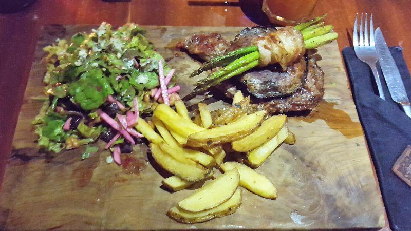 Cafe Vida Canggu. Ribeye Steak serviert mit Hauspommes, grünem Salat und grünem Spargel im Speckmantel.