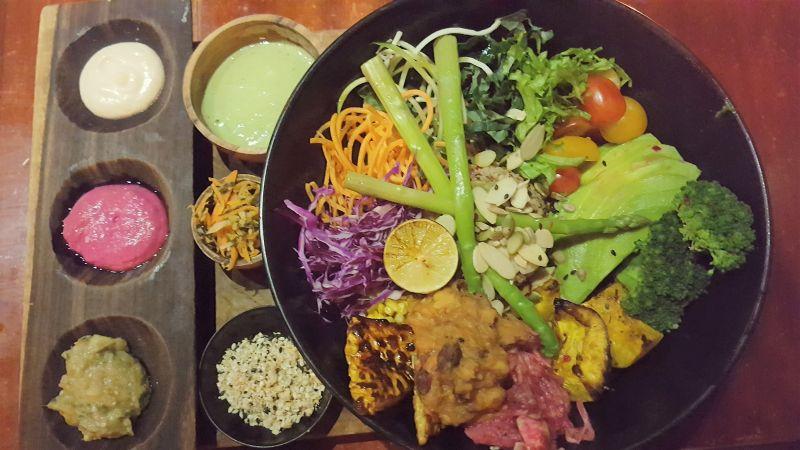 Cafe Vida Canggu. Healthy Bowl bestehend aus grünem Spargel, Broccoli, Avocado, Rotkohl, Karotten, grünem Salat, sautiertem Gemüse, gegrilltem Tempe und einigem mehr. Dazu ein paar Saucen und ein Schälchen Sauerkraut.