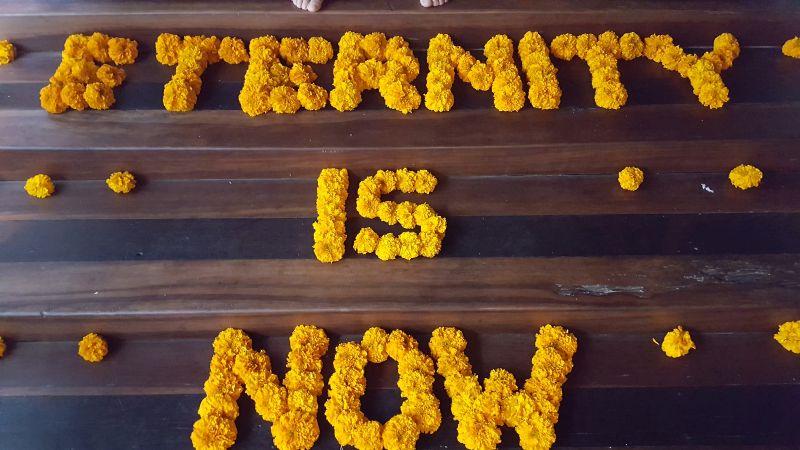 """Clear Café. Stufen mit Blumen. Auf den Stufen zum Spa- und Toilettenbereich ist zu lesen """"Eternity is now"""" aus lauter orangen, aneinandergereihten Blüten."""