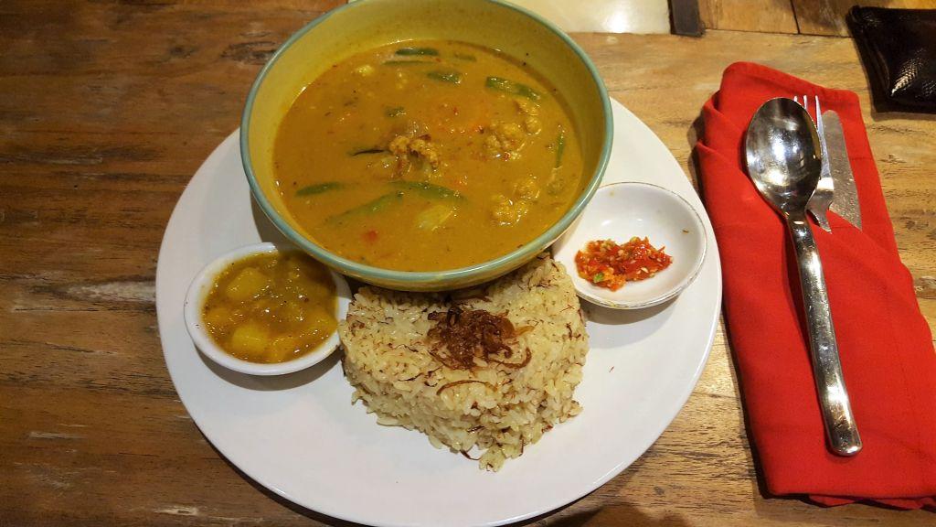 Essen in Ubud. Clear Café. Gemüse Curry in einer Schüssel auf einem großen Teller, auf dem eine Portion Reis in Herzform und zwei kleine Schälchen mit Chutneys stehen.