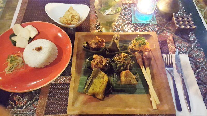 Essen in Ubud. Gedong Sisi Warung. Nasi Campur. Zusammenstellung indonesischer Gerichte. Rindereintopf, balinesisches Hühnergeschnetzeltes, Hühnerhackspiese, balinesisches Gemüse und Sambal Matah Soße mit Reis.