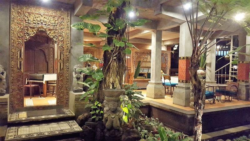 Essen in Ubud. Gedong Sisi Warung. Einrichtung. Gefliester Boden, Steinstatuen, Pflanzen, Tür mit Holzschnitzereien, alles nach außen offen.