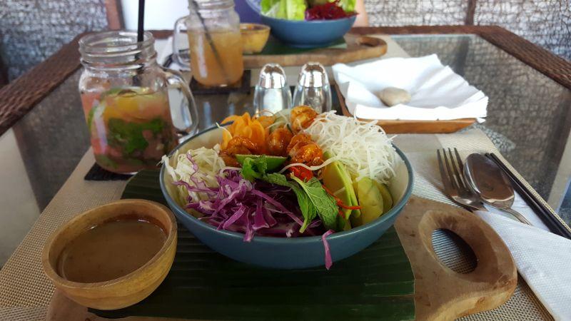 Green Spot Cafe Canggu. Bowls und Limonaden. Im Vordergrund die Shrimp Bowl, dahinter Salz- und Pfefferstreuer, zwei Gläser mit Limonade und im Hintergrund die Falafelbowl.