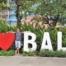 I love Bali. Foto von mir zwischen den mannshohen Buchstaben weißes I, rotes Herz und BALI in weiß auf einem Parkplatz in Seminyak.