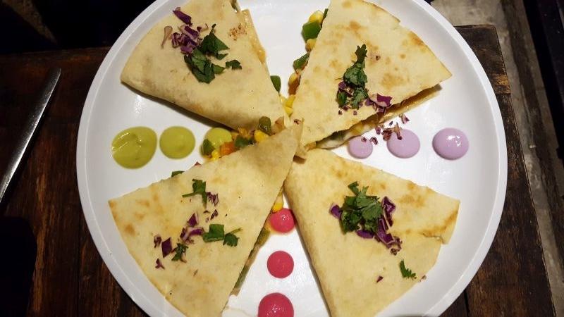 Essen in Ubud. Lazy Cats. Cheeseadilla. Quesadillas auf einem Teller, zwischen den einzelnen Segmenten bunte Soßenkleckse.