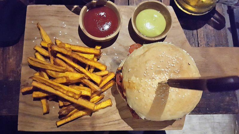 Essen in Ubud. Lazy Cats. BBQ Tempe Burger. Süßkartoffelpommes, zwei Soßen in kleinen Schälchen und der Burger, mit einem Messer aufgespiest, auf einem Holzbrett.