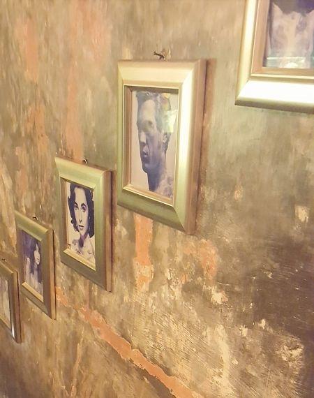 Lazy Cats. Wand mit Bildern. Treppen mit gerahmten Porträtfotos. Die Wand ist unverputzt, fleckig und schaut sehr alt aus.