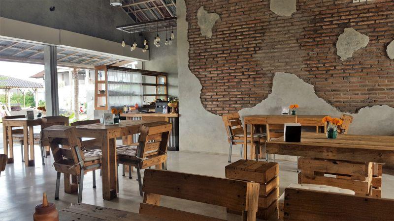 Makan Warung Canggu. Ambiente. Tische, Stühle und Hocker aus Holz und Metall. Die Wand teilweise unverputzt, sodass man die Ziegel erkennt. Nach links ist das Gebäude offen, von hier aus betritt man das Restaurant.